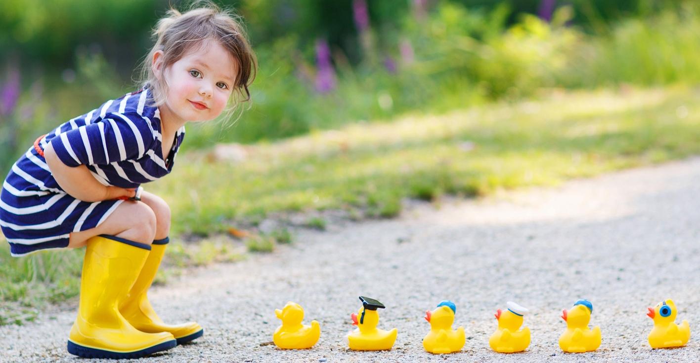 Little Girl With Rubber Ducks In Summer Park